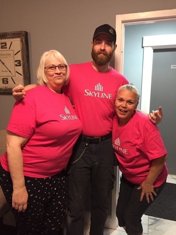 Three Skyline staff in Nova Scotia wear pink shirts