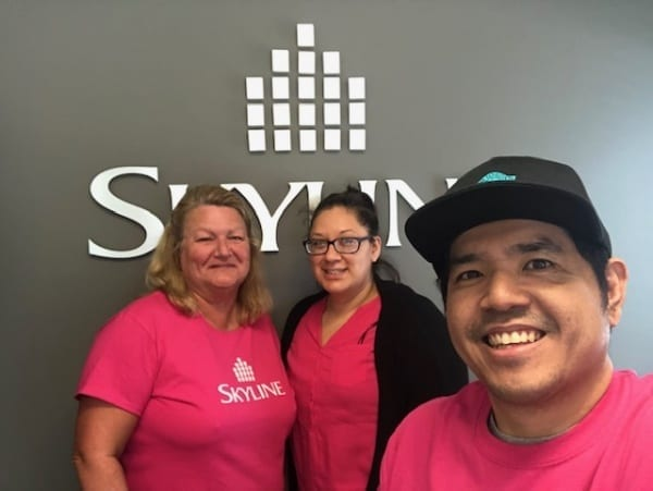 Three Skyline staff in Alberta wear pink shirts