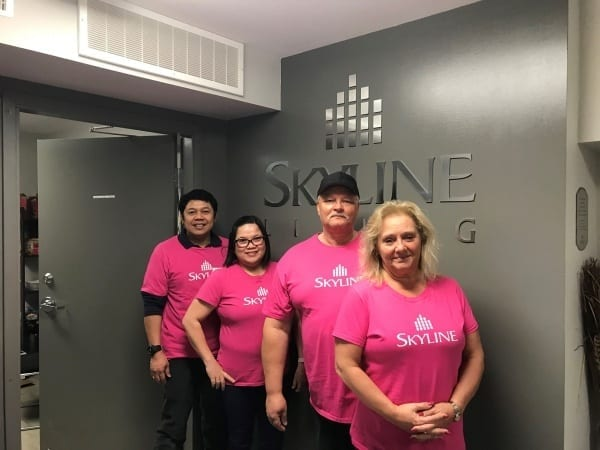 Four Skyline staff in Winnipeg wear pink shirts